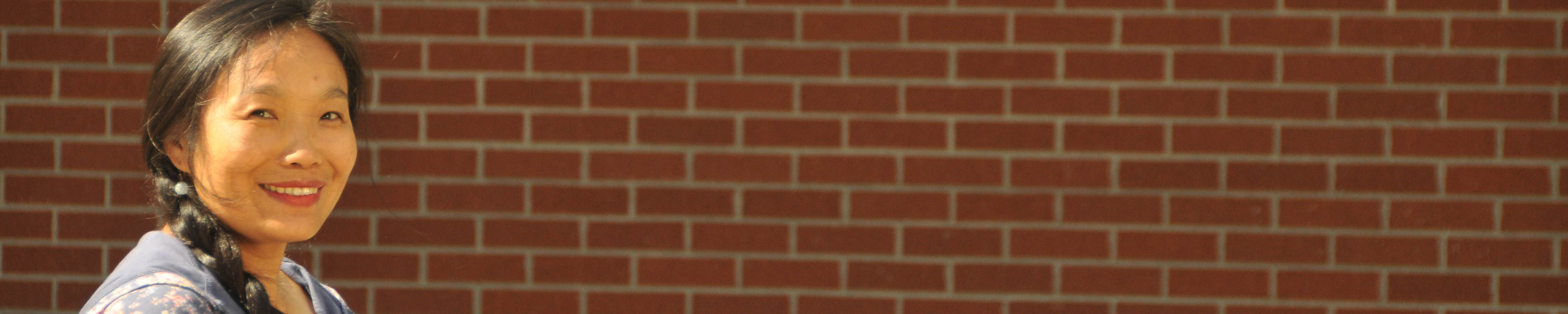Asian woman in front of brick wall on college campus